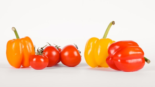 Red and yellow peppers with tomatoes on white
