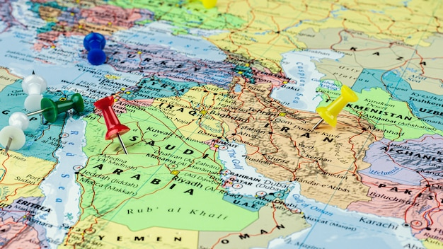 Red and yellow pin placed at saudi arabia and iran map.