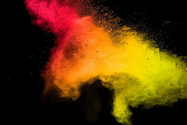 Red yellow powder explosion cloud on black background.