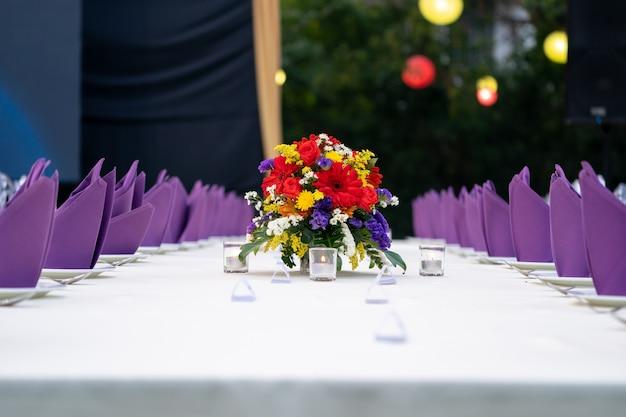 빨간색-노란색-보라색-흰색 꽃 부케가 긴 흰색 덮개 테이블에 놓여 있으며 정원 필드에서 호화로운 저녁 식사를 준비합니다.