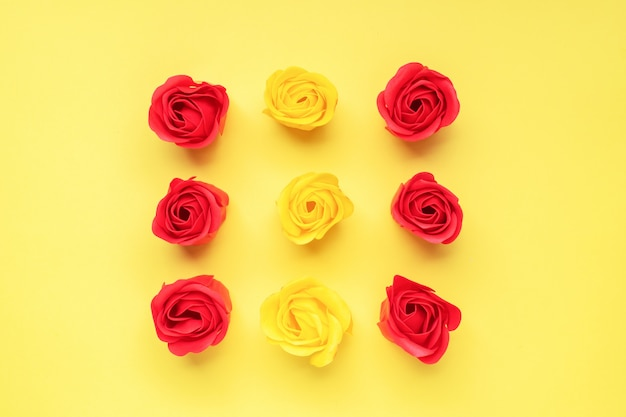 Red and yellow rose buds on a yellow background. the concept of valentine's day, wedding romance. flat lay copy space.