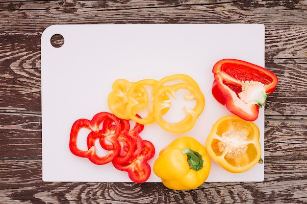 Red and yellow slices of bell pepper on white chopping board over the wooden desk