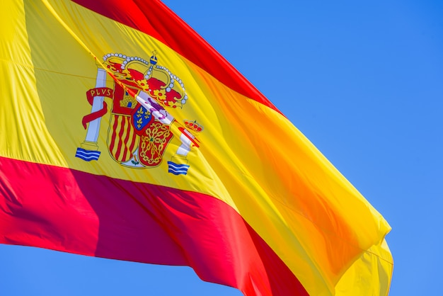 Red and yellow spain flag with royal shield waving in the wind isolated against blue sky