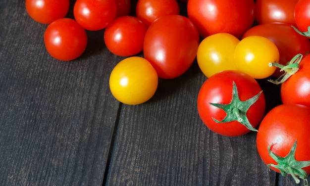 Red and yellow tomatoes on a dark table, fresh tomatoes on an old wooden table,growing vegetables,healthy food, vegetarian food, selling tomatoes