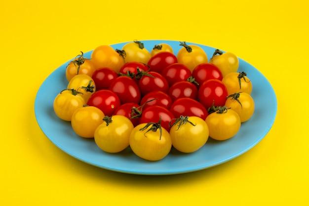 Piatto blu allineato maturo fresco dei pomodori gialli rossi sul giallo