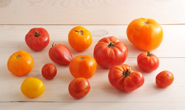 Red and yellow tomatoes on wooden white surface