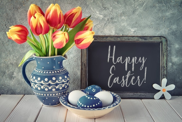 Red-yellow tulips in blue ceramic pitcher with easter eggs and a blackboard on gray wall, text
