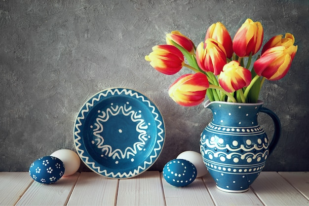 Red-yellow tulips in blue ceramic pitcher with easter eggs and a blackboard on gray