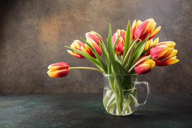 Red yellow tulips in glass vases. a gift for woman's day. greeting card for mother's day. celebrating easter. copy space