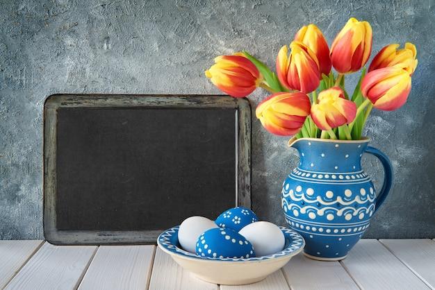Красно-желтые тюльпаны в синем керамическом кувшине с пасхальными яйцами и доской на сером фоне