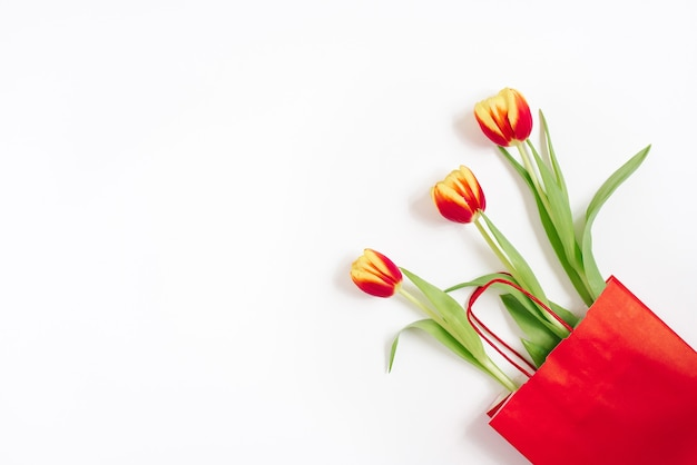 Red and yellow tulips in a red gift bag on a white background with copying space