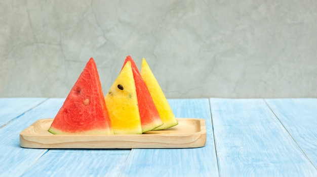 Red and yellow watermelon on a plate and blue wooden table.