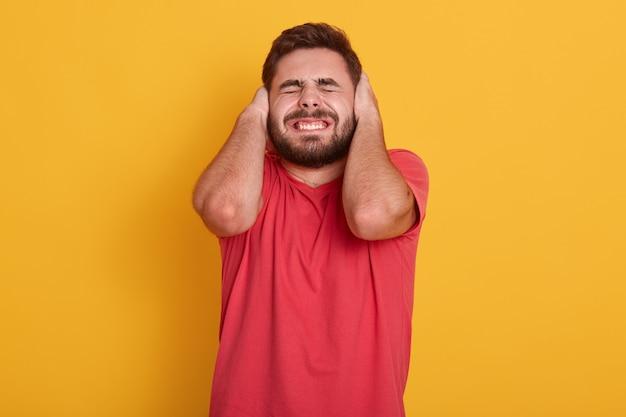 ハンサムなひげを生やした男性redcasual tシャツを着て、目を閉じて耳でポーズをとって魅力的な男性は、大きな音を聞いて、立っている男は黄色に分離されました。人のコンセプトです。