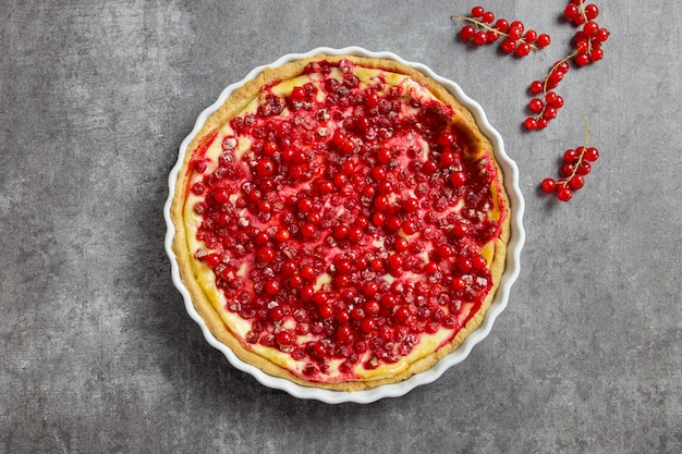 Чизкейк из красной смородины, пирог со свежими ягодами в белой форме для выпечки на темно-сером фоне.