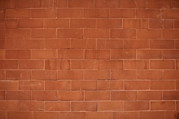 赤みがかったオレンジ色のレンガの壁のテクスチャ背景