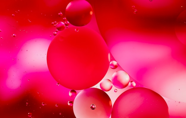 Reddish shades of oil drops on a water surface abstract background