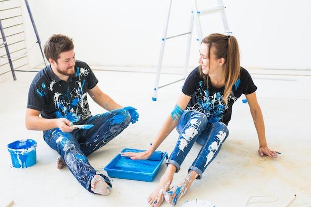 模様替え、色、リノベーション、人々のコンセプト – 夫婦が壁を塗り、色を混ぜて楽しんでいる