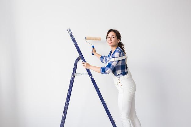 改装、リフォーム、新しい家と人々のコンセプト-自分で修理をしている女性画家