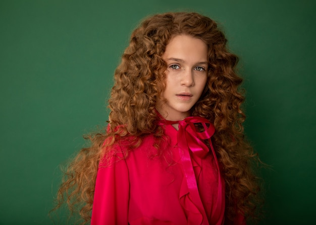 Redhair beautiful girl with curly afro curls in bright pink blouse on green background.
