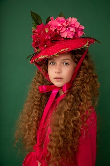 Redhair beautiful girl with curly afro curls in bright pink dress on green background.