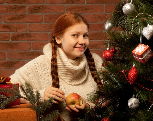 Redhair christmas woman wit apple.