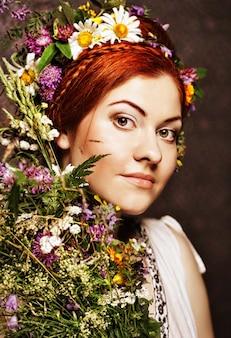 彼女の髪に大きな髪型と花があり、花束の花がある赤毛モデル。