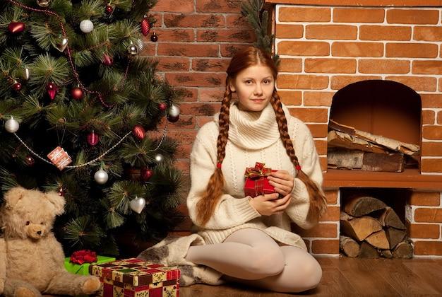 Рыжая женщина с рождественским подарком в интерьере дома