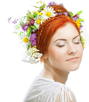 彼女の髪に大きな髪型と花を持つ赤毛の女性。