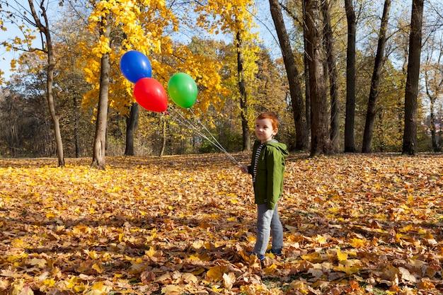 赤緑と青の風船と秋の公園を歩いて緑のジャケットを着た赤毛の少年