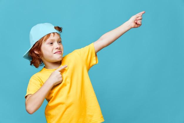 色付きの壁にポーズをとって黄色のtシャツを着た赤毛の少年