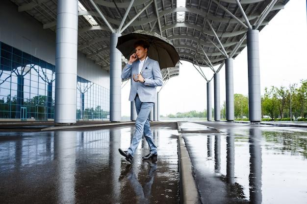 Рыжий бизнесмен с зонтиком разговаривает по телефону