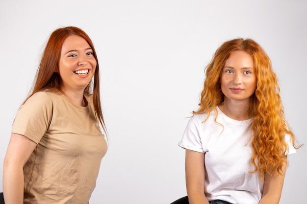 Рыжеволосые милые подруги на белой стене улыбаются и позируют