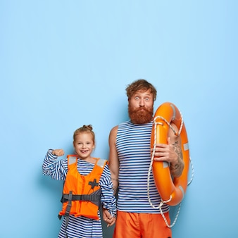 Redhaired 딸과 아버지는 수영 장비와 함께 포즈