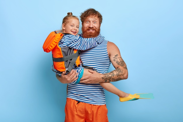 Рыжая дочь и отец позируют вместе с плавательными принадлежностями