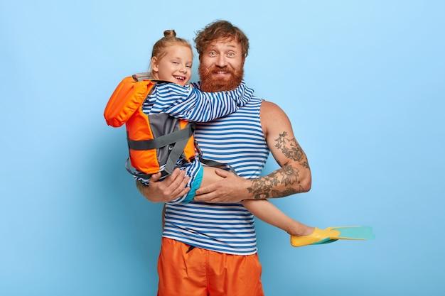 Figlia e padre dai capelli rossi posano insieme all'attrezzatura per il nuoto