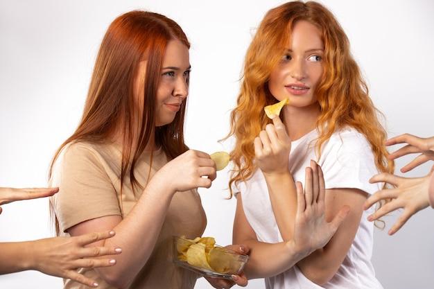 Redhaired 여자 친구는 흰 벽에 간식을 향해 많은 손으로 감자 칩 사진을 공유하고 싶지 않습니다.
