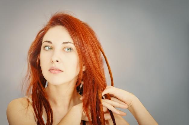 Рыжая девушка расчесывает дреды пальцами в стиле бохо или прическа хиппи, женщина с косичками из к ...