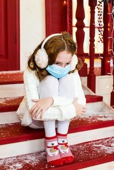 Рыжая девушка в медицинской маске грустит в канун рождества