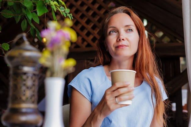 A redhaired girl is relaxing with a cup of coffee or tea in a summer cafe