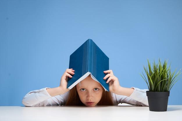 Рыжая девушка сидит за школьным столом с книгой в руках образование