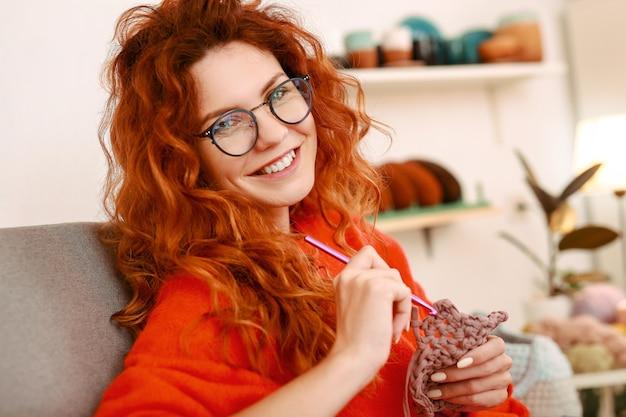 넓게 웃고 redhaired 소녀는 뜨개질 스틱을 들고 안심 y 느낌