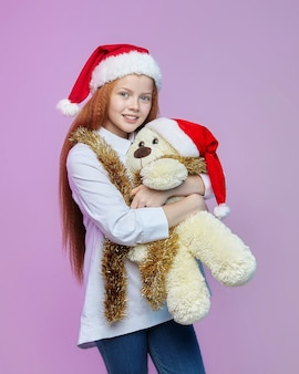 Redhaired girl and a teddy bear in a santa hat