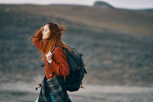 バックパックを背負った赤毛の旅行者が山の自然を振り返る