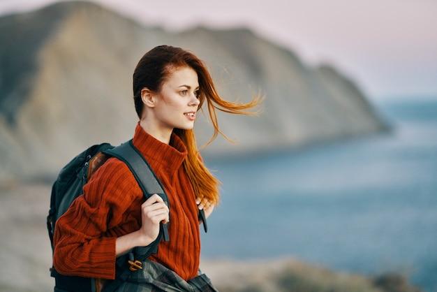 Рыжая путешественница с рюкзаком на спине в свитере на пляже в горах недалеко от