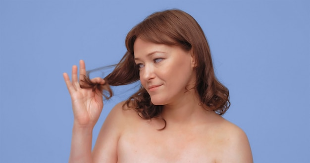 Redhaired woman holds and looks at split ends of her hair adult lady with naked shoilders cut out on...