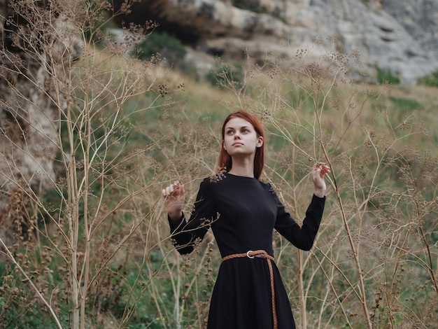 黒いドレスを着た赤毛の女性が森の中で秋の自然の上を歩いています