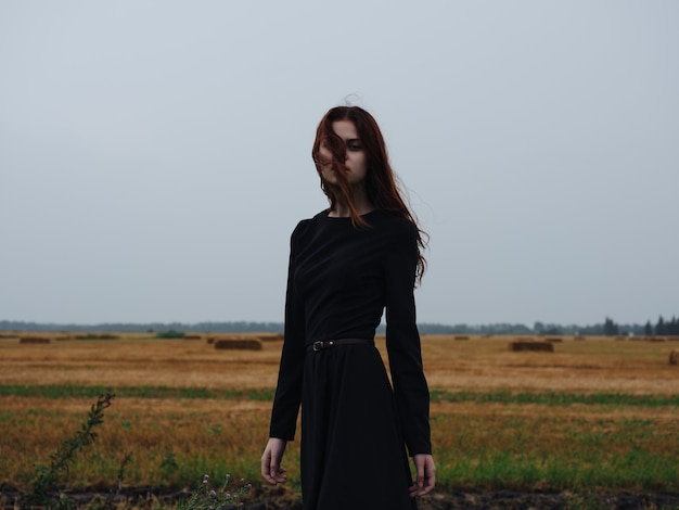 風景をポーズするフィールドの黒いドレスの赤髪の女性