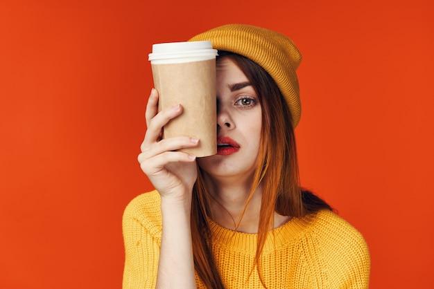 모자를 쓴 redhaired 여자는 스웨터를 입고 커피 한 잔의 라이프스타일 빨간색 배경을 가지고 있습니다.