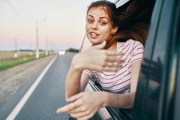 Tシャツを着た赤毛の女性が車の窓から外を見て、夏に手でジェスチャーをする