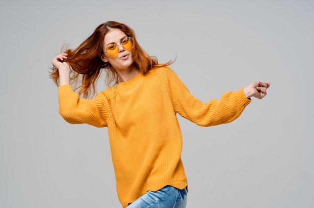 노란색 스웨터 패션 안경 스튜디오 모델에서 redhaired 여자